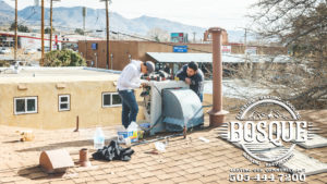 two guys on a roof working on a broken ac unit in albuquerque new mexico