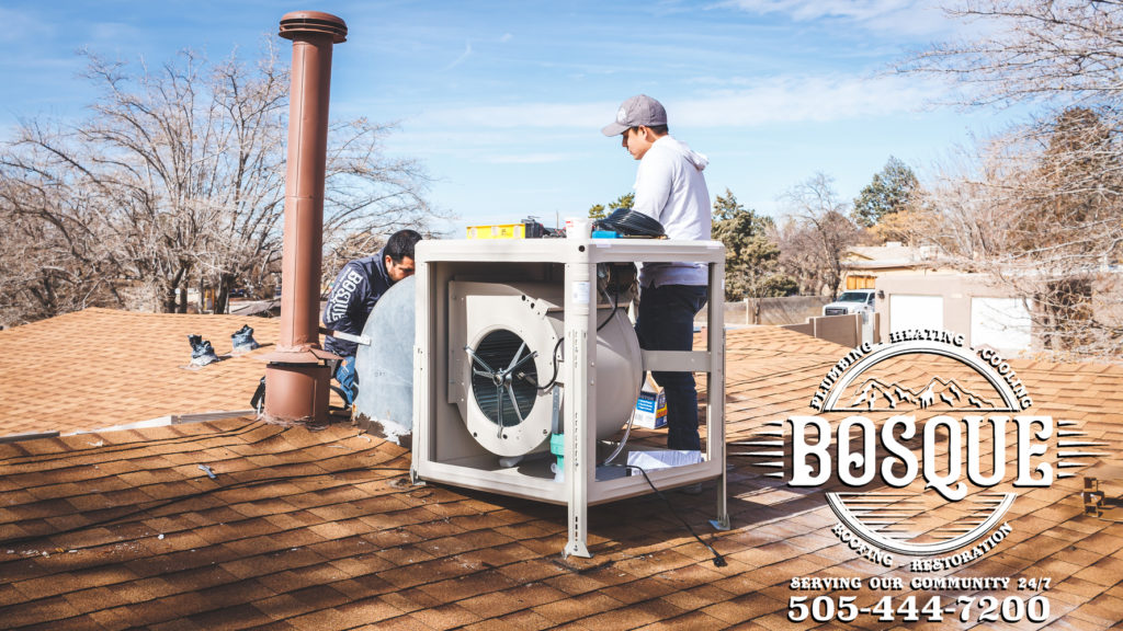 two bosque HCP employees doing air conditioning service on a roof
